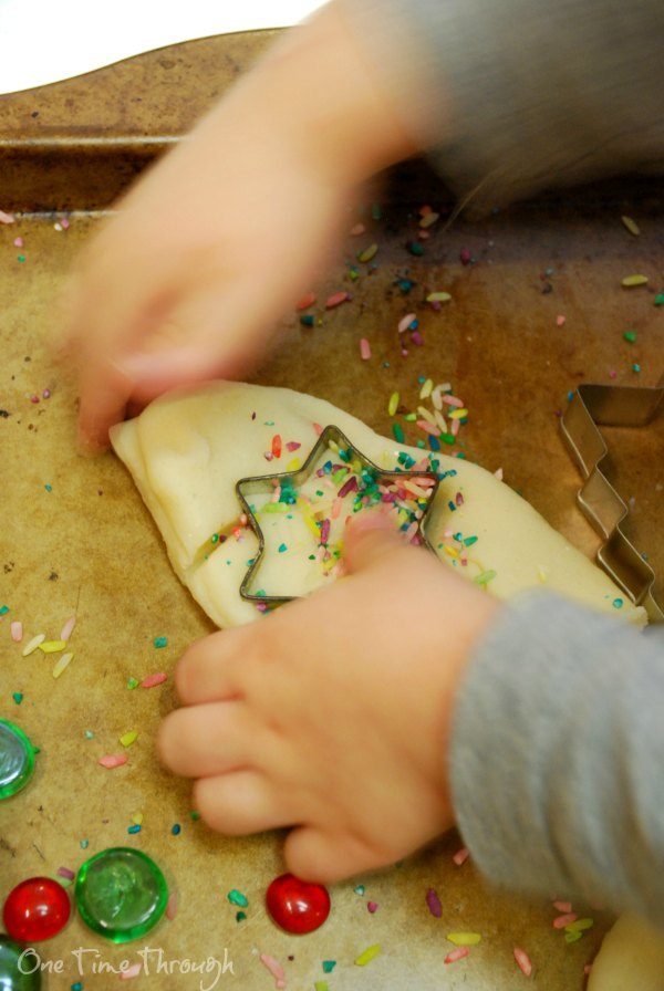 cutting out stars of confetti playdough