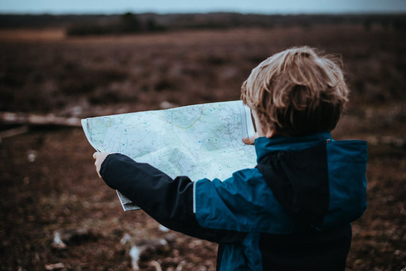 This picture shows a boy studying a map and is part of a post about perfectionism in kids.